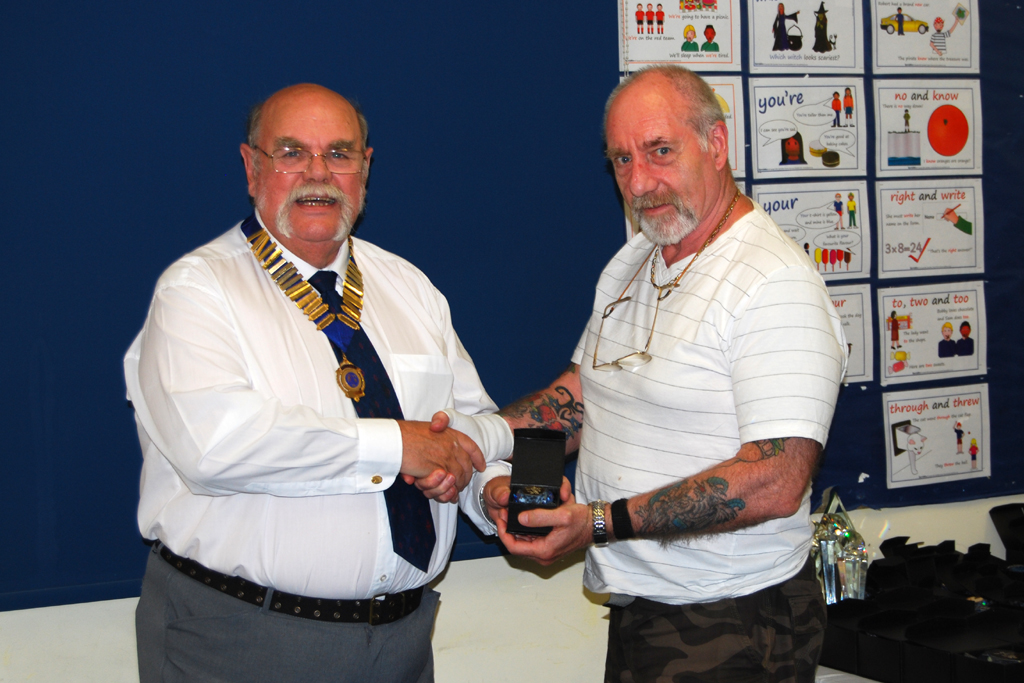 Tony G4STP is presented with his Sapphire Award trophy by Geoff G7GJU